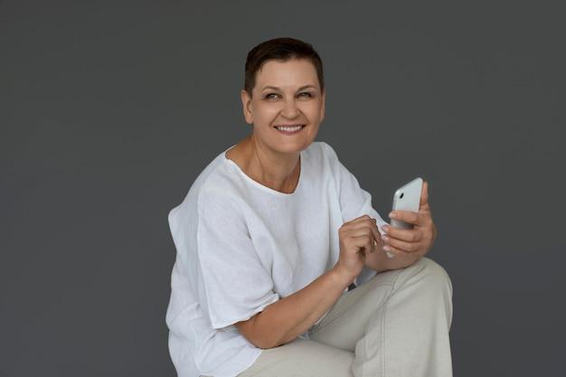 Medium shot senior woman holding device