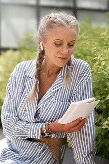 Средний выстрел старшая женщина, читающая книгу