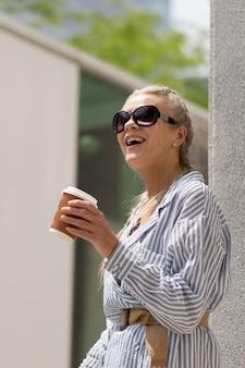 커피 컵을 가진 중간 샷 수석 여성