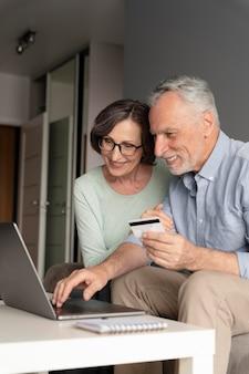 Anziani a tiro medio con laptop e card