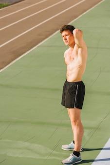 Medium shot of shirtless body builder