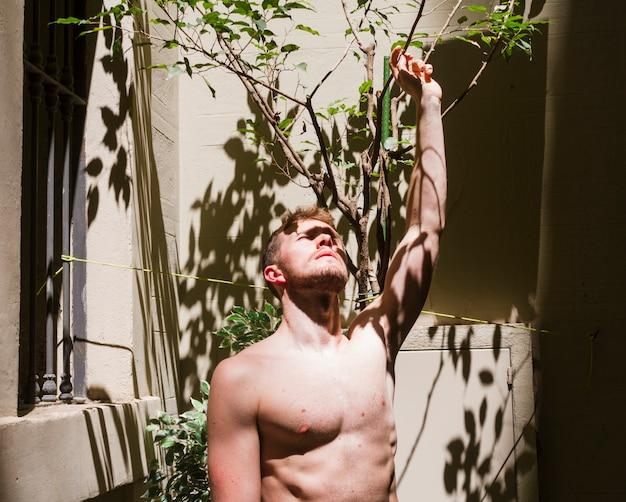 Medium shot shirtless man looking up