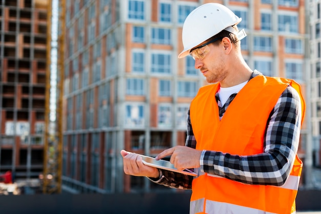 Medium shot side view construction engineer using tablet