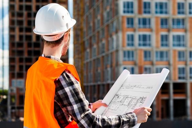 Medium shot side view of engineer holding plans