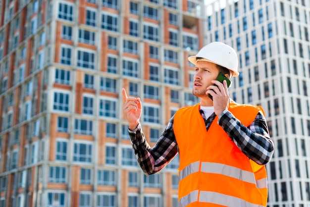 Medium shot side view of engineer talking on the phone