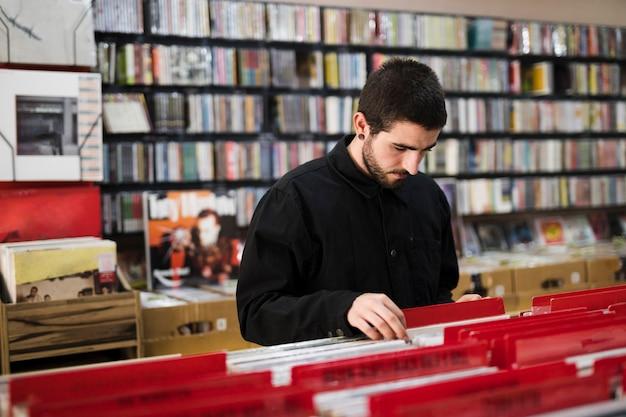Medium shot side view of young man looking for vinyls in store