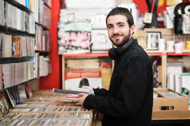 Medium shot side view of young man in music store looking at camera