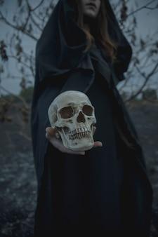 Medium shot of sideways man holding a skull