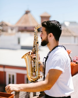 Medium shot sideways man posing with saxophone