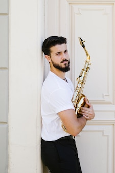 Medium shot sideways man posing with saxophone
