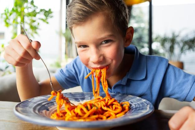 스파게티를 먹는 중간 샷 웃는 소년