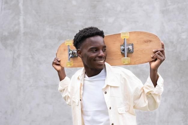 Medium shot smiley boy holding skateboard