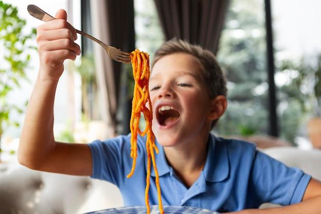 スパゲッティとミディアムショットのスマイリーボーイ