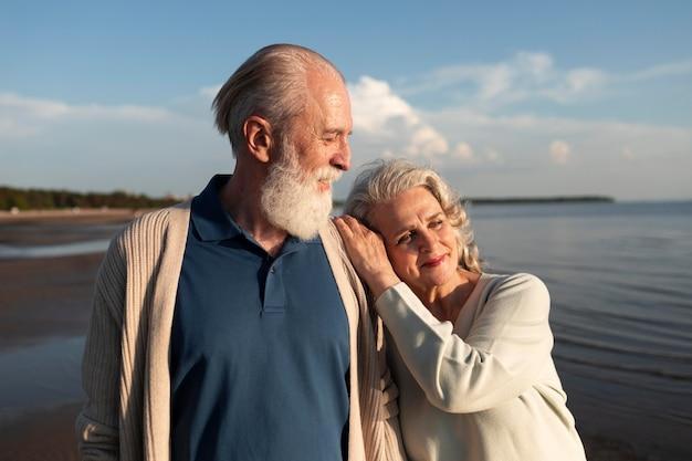 해변에서 중간 샷 웃는 커플