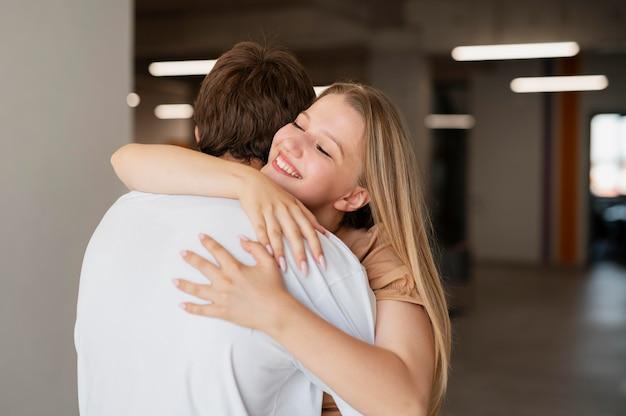 중간 샷 웃는 커플 포옹