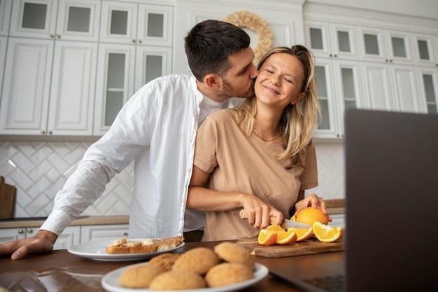 Coppia sorridente di colpo medio in cucina
