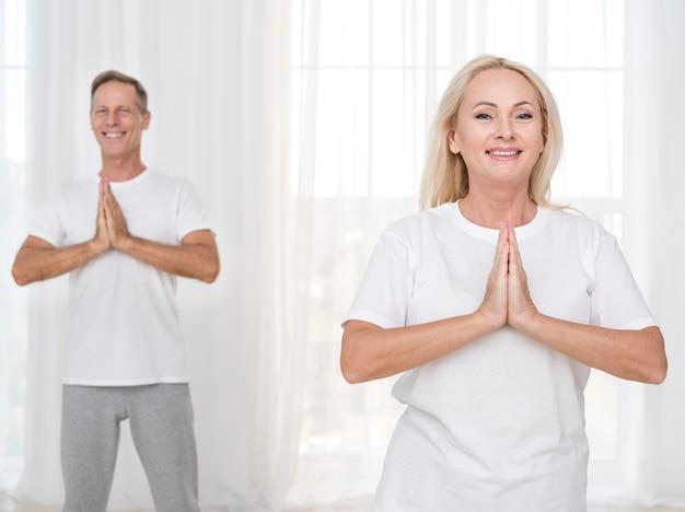 Средний выстрел смайлик пара медитирует вместе