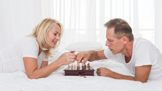 Medium shot smiley couple playing chess