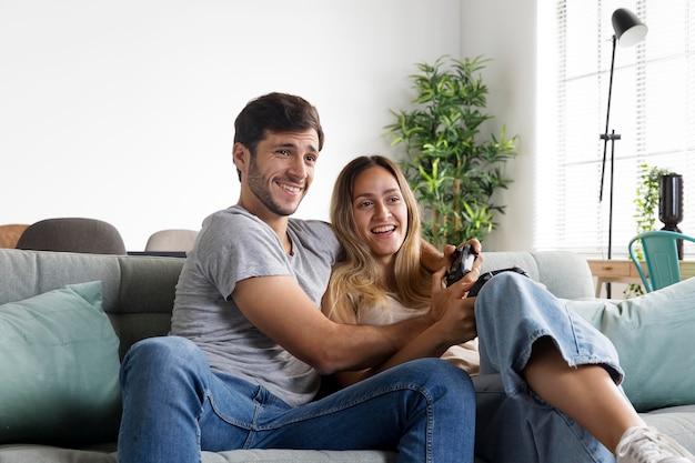 ビデオゲームをプレイするミディアムショットのスマイリーカップル