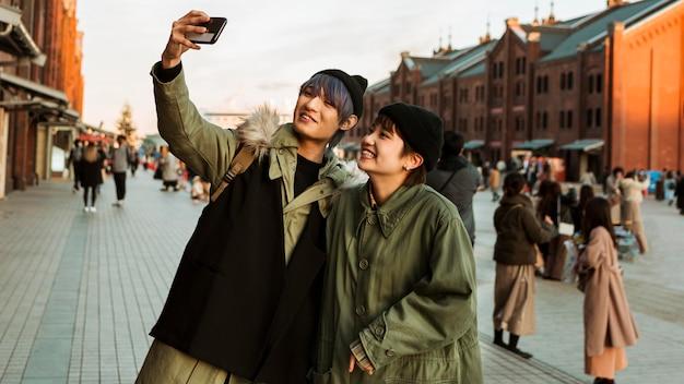 ミディアムショットのスマイリーカップルが自分撮りを撮る
