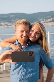 Medium shot smiley couple taking selfie