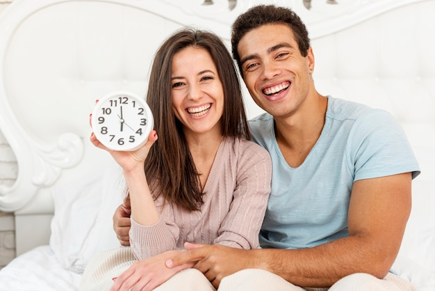 Medium shot smiley couple with clock