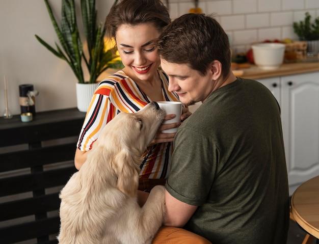かわいい犬とミディアムショットのスマイリーカップル
