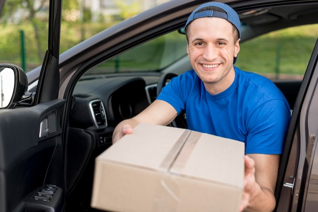 Medium shot smiley delivery guy in car