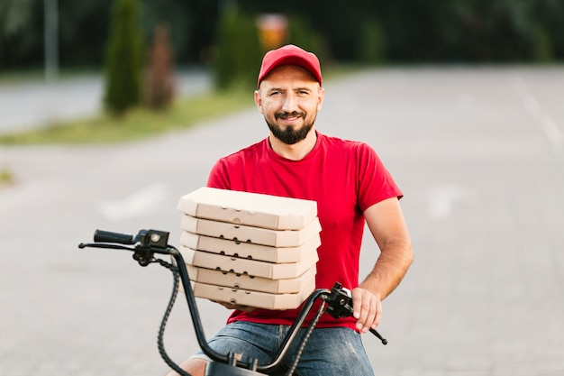 Medium shot smiley delivery guy holding pizza boxes