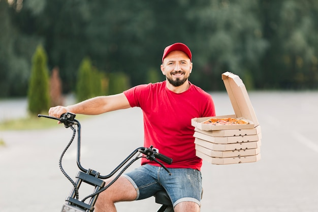 Medium shot smiley delivery guy on motorcycle