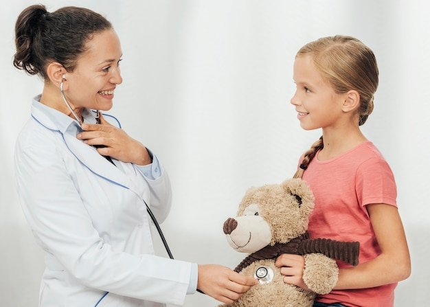 Medium shot smiley doctor and kid