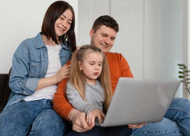 중간 샷 웃는 가족 노트북