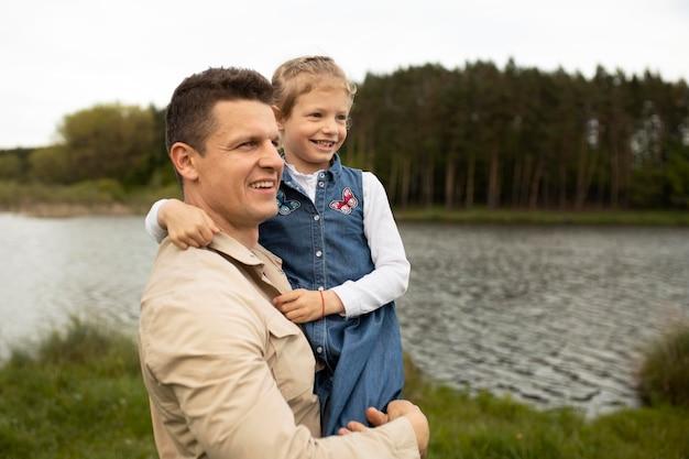 Medium shot smiley father holding child