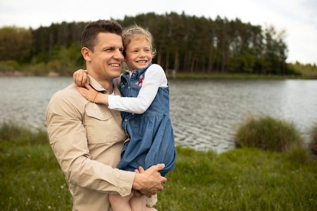 Padre sorridente con colpo medio che tiene bambino