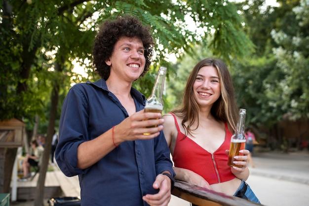 飲み物とミディアムショットの笑顔の友達