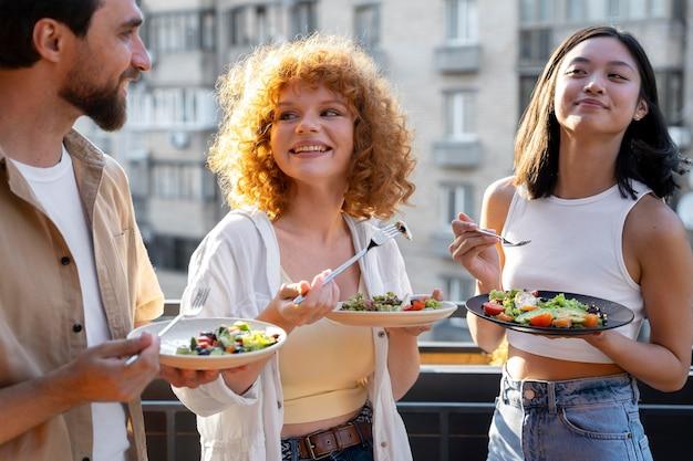 Улыбающиеся друзья среднего кадра с едой