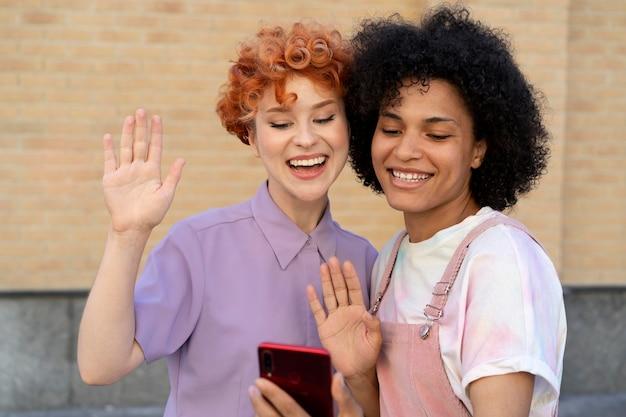 Улыбающиеся друзья среднего кадра со смартфоном