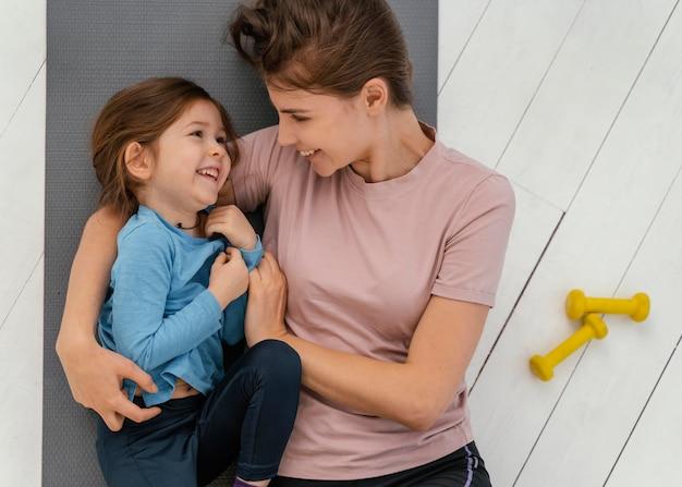 ミディアムショットのスマイリーガールと母親