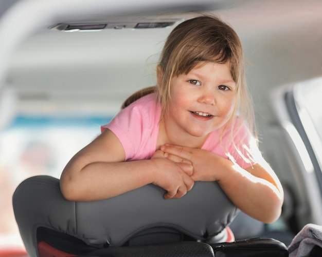 Medium shot smiley girl in car
