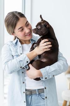 Улыбающаяся девочка среднего выстрела с милой собакой