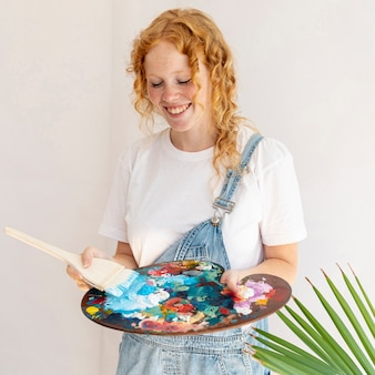 Medium shot smiley girl holding painting palette