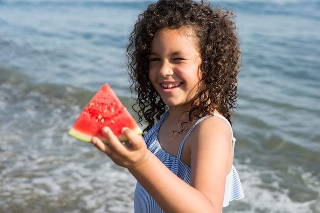 Medium shot smiley girl holding watermelon
