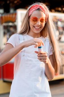 Улыбающаяся девочка среднего кадра делает мыльные шары