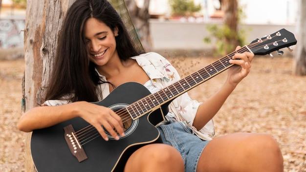 Улыбающаяся девочка среднего кадра, играющая на гитаре
