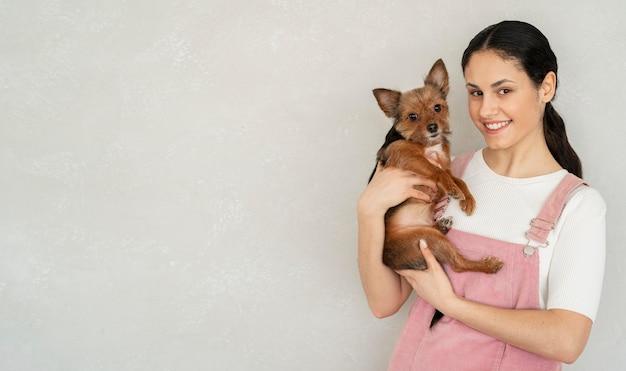 Улыбающаяся девушка среднего выстрела позирует с собакой