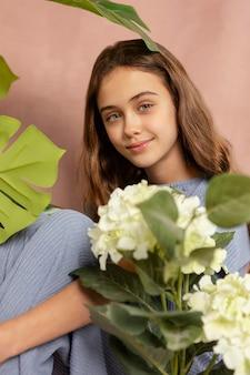 꽃과 함께 포즈를 취하는 중간 샷 웃는 소녀