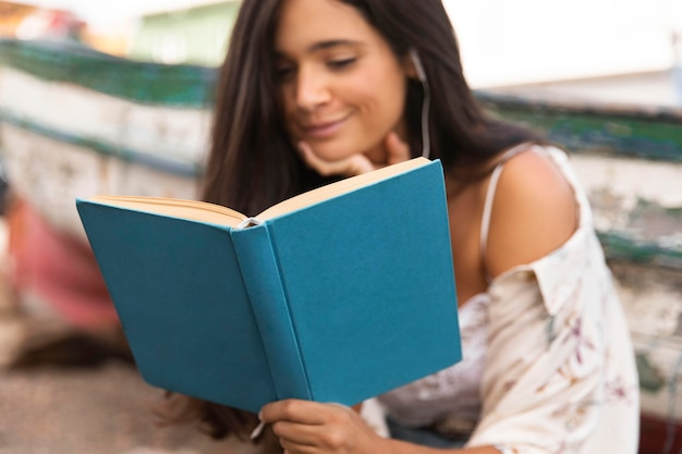 Medium shot smiley girl reading book