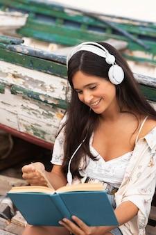 Улыбающаяся девочка среднего кадра читает книгу