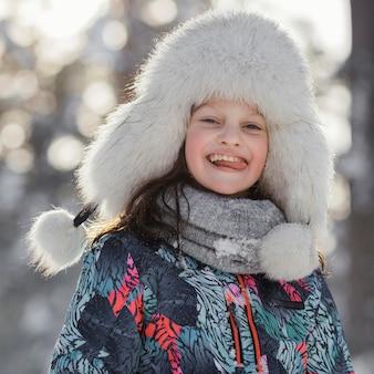Medium shot smiley girl wearing hat