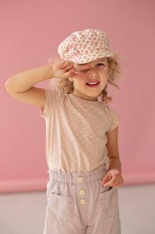 Ragazza sorridente con colpo medio che indossa un cappello